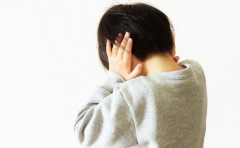 親に怒られて耳を塞ぐ男の子