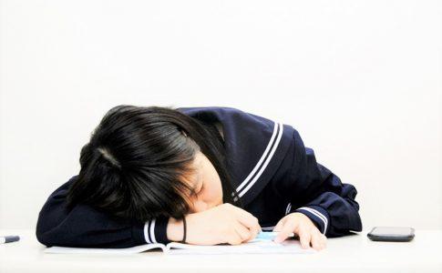 机で寝る中学生
