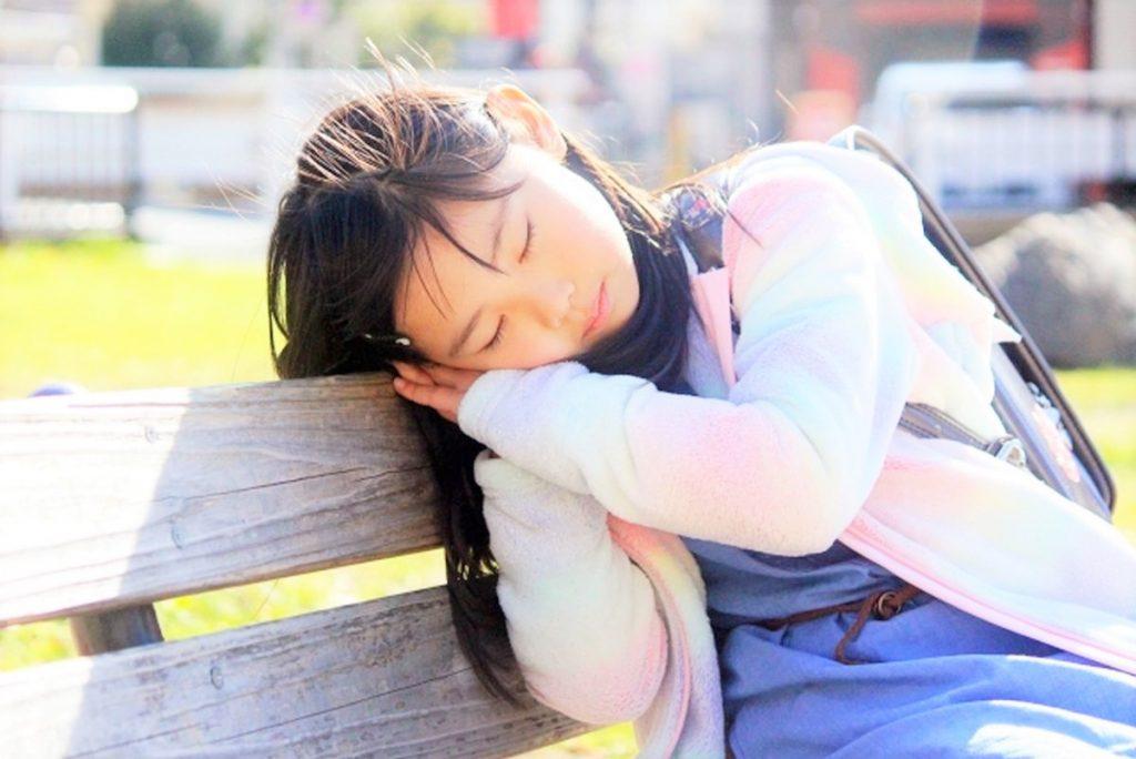 ベンチで寝る小学生の女の子