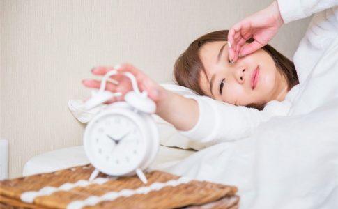 朝起きて目覚まし時計を止める女性