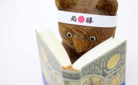 必勝のハチマキをした本を読む木彫りのクマ
