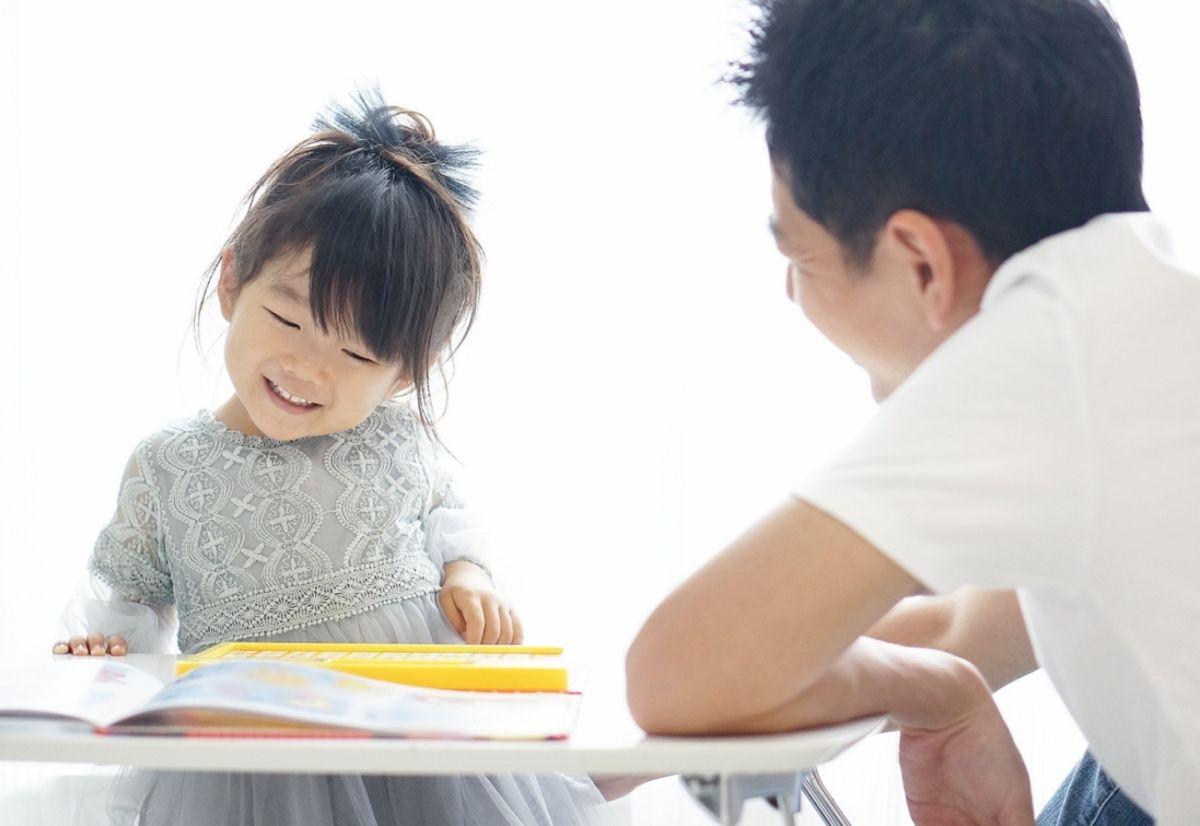 子どもと一緒に本を読む笑顔の親子