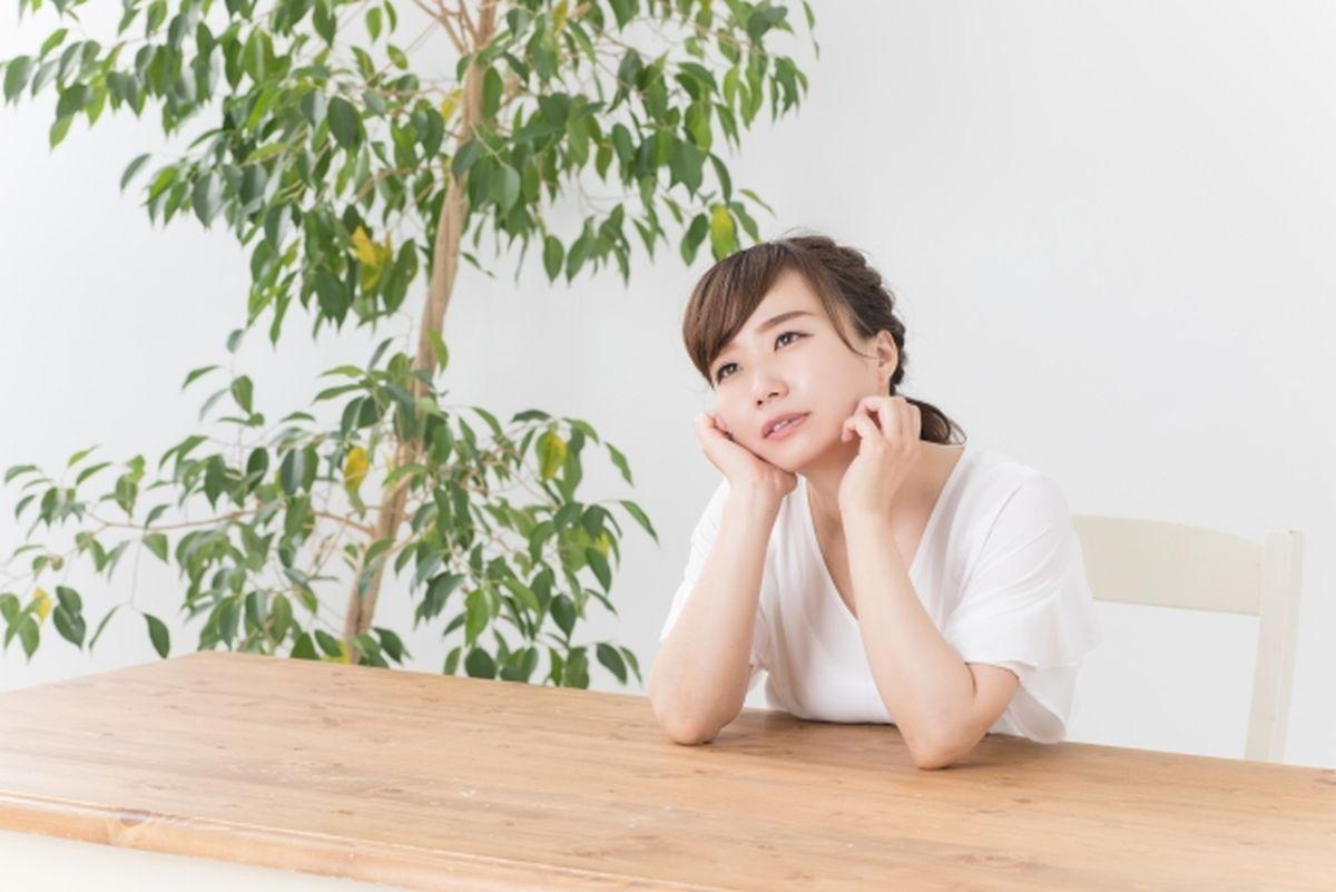 憂鬱で机に肘をつく女性