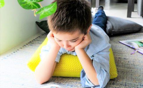寝転がって読書をする少年