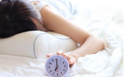 目覚まし時計を止めたまま二度寝する女性
