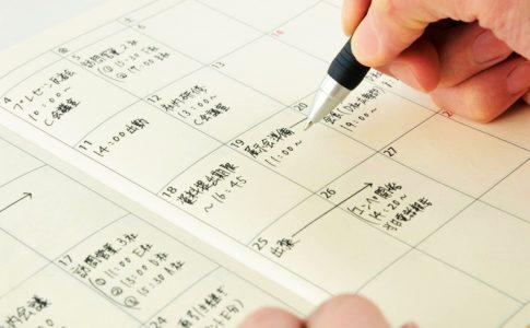 スケジュール手帳に予定を書き込む様子